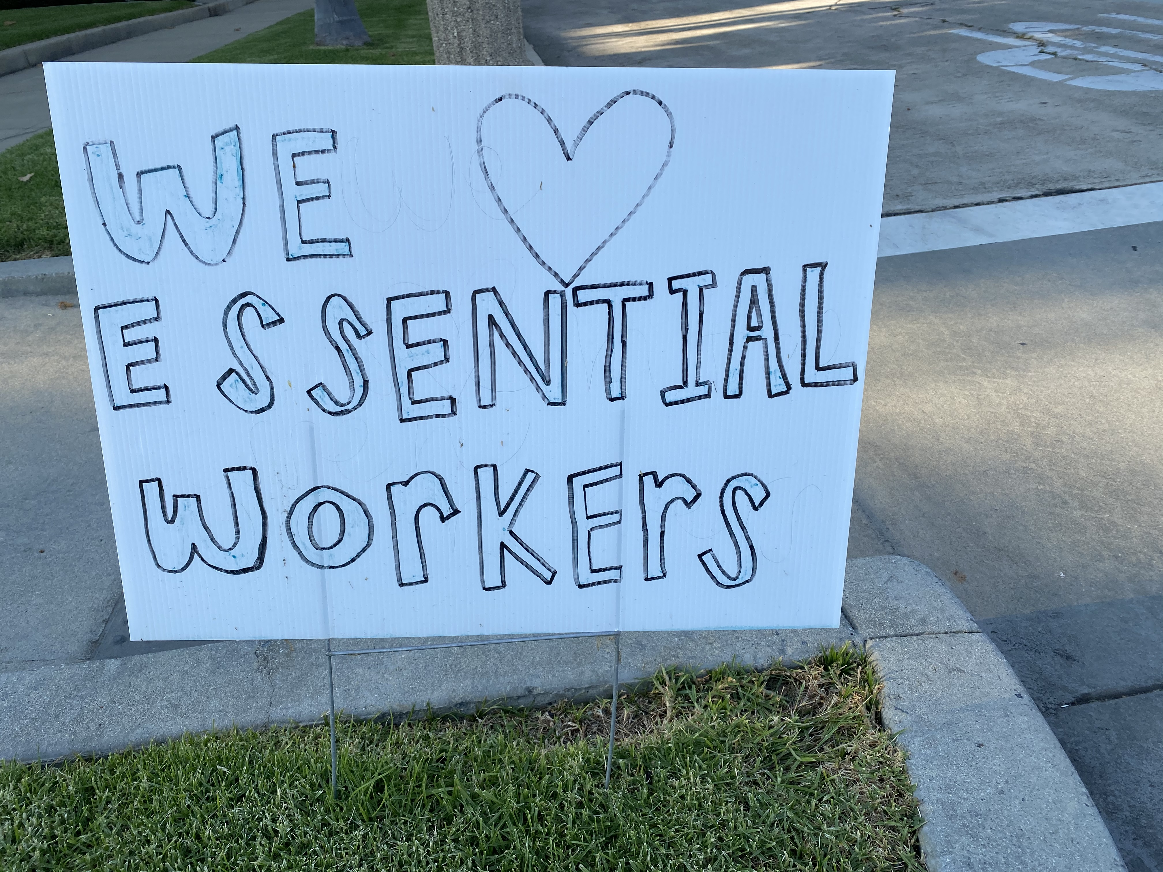 Home made Sign that says we love our essential workers.