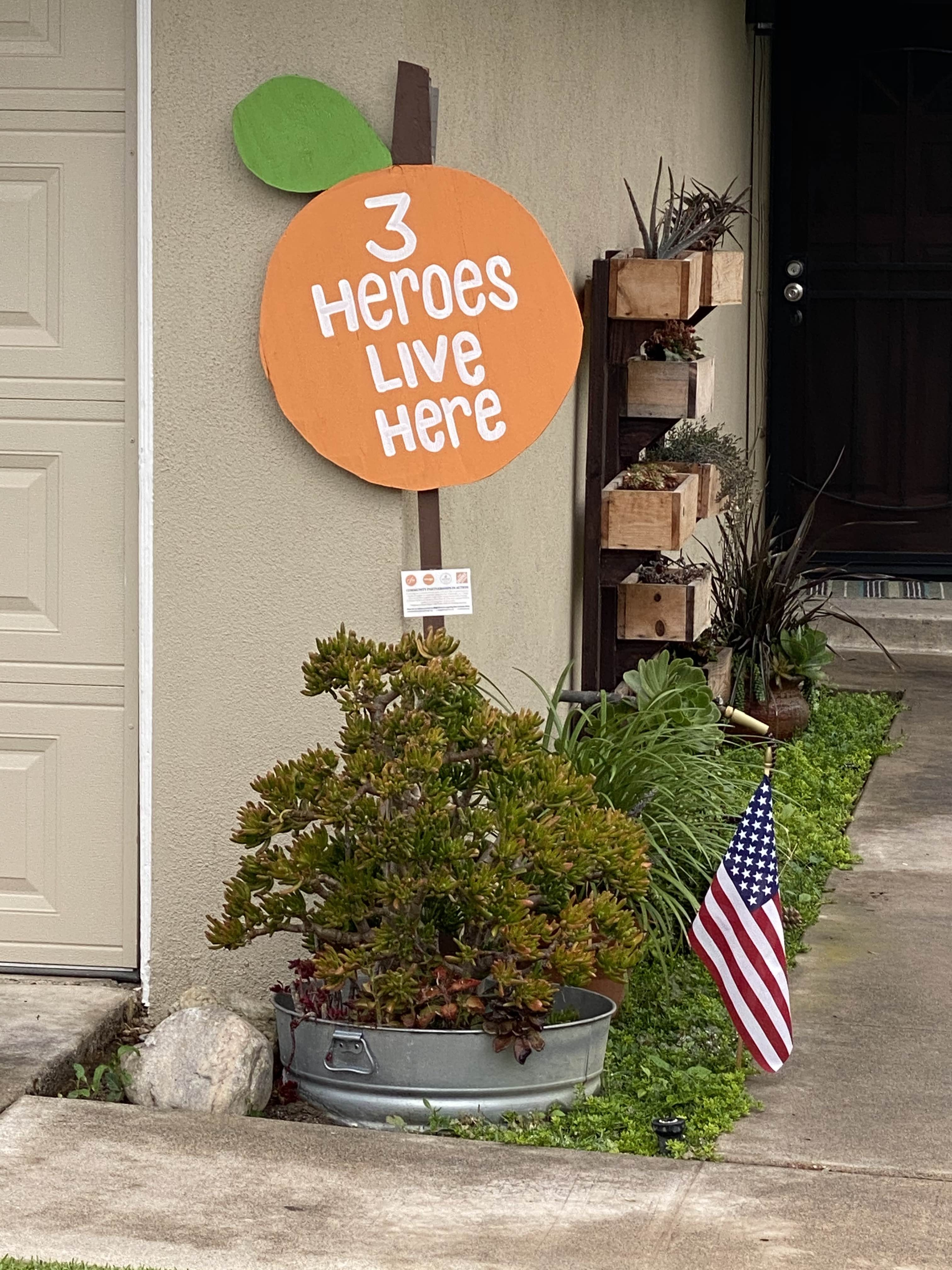 """Picture of  sign in the shape of an Orange with white text that says """"3 Heroes Live Here""""."""
