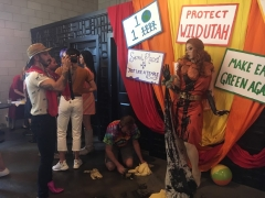 A drag queen dressed as red rocks poses for a photographer. Her red rock dress is covered in black paint representing oil. Behind the drag queen is a colorful backdrop with signs supporting public lands preservation.