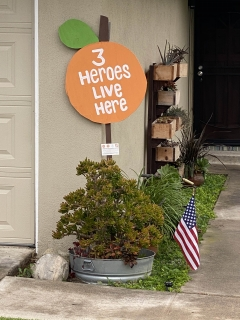 "Picture of  sign in the shape of an Orange with white text that says ""3 Heroes Live Here""."